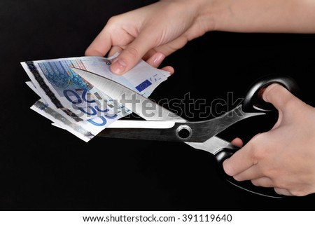 Hands with scissors cutting Euro banknotes, on black background - stock photo
