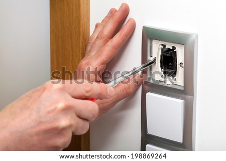 Hands with screwdriver repairing a light switch - stock photo