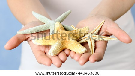 hands with starfishes - stock photo
