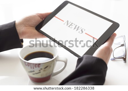Hands with tablet and coffee reading news - stock photo
