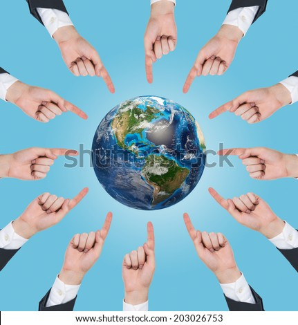 Hands with the forefinger pointing to the continent of north America on a globe of planet earth, over blue background. Elements of this image furnished by NASA