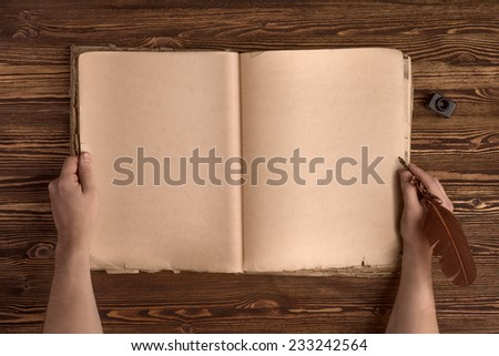 hands with vintage quill pen, ink and old book on wooden table background - stock photo