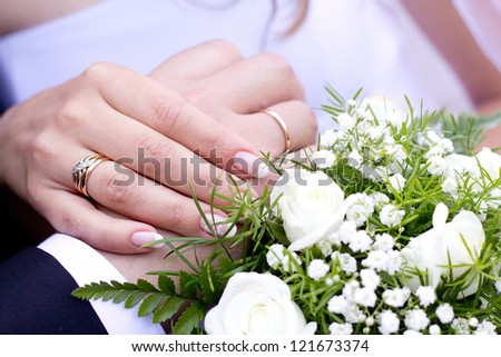 Hands with wedding rings and wedding bouquet - stock photo