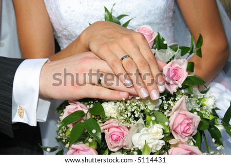 Hands with wedding rings on the flowers background - stock photo