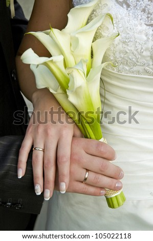 Hands with wedding rings on wedding bouquet - stock photo