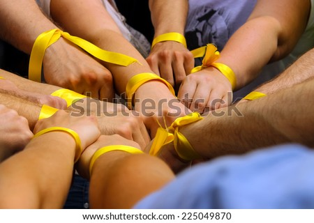 Hands with yellow ribbons together. The concept of the unity of sport - stock photo