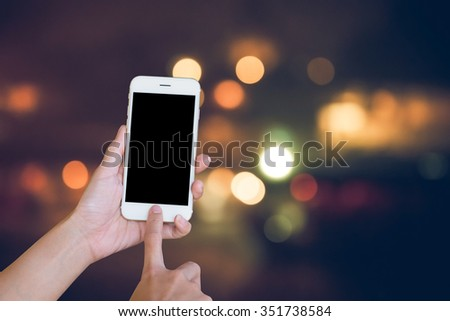 Hands woman are holding touch screen smart phone,tablet  on night glitter sparkle defocused rays lights bokeh abstract background.