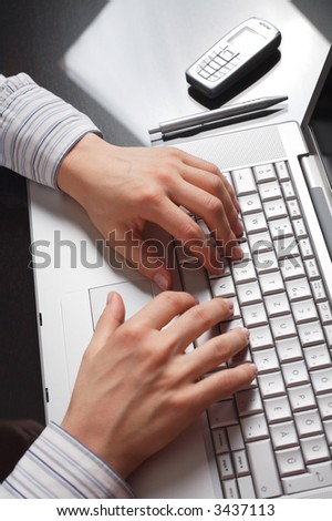 Hands work on a laptop computer.