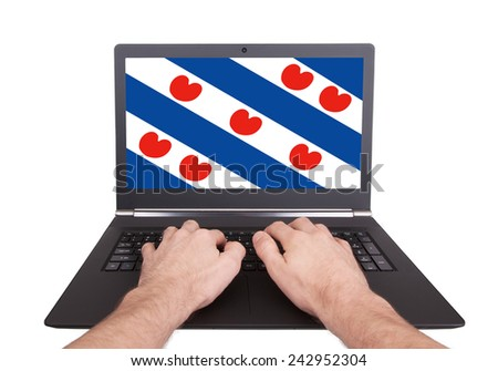 Hands working on laptop showing on the screen the flag of Friesland - stock photo