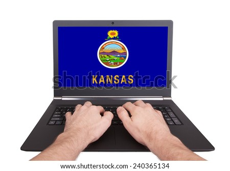 Hands working on laptop showing on the screen the flag of Kansas - stock photo