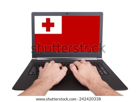 Hands working on laptop showing on the screen the flag of Tonga