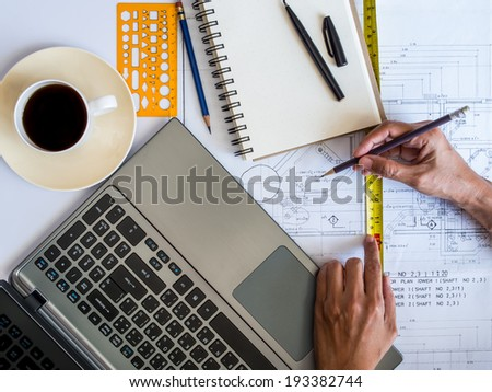 Hands working on notepad with architectural blueprint / tools and laptop - stock photo