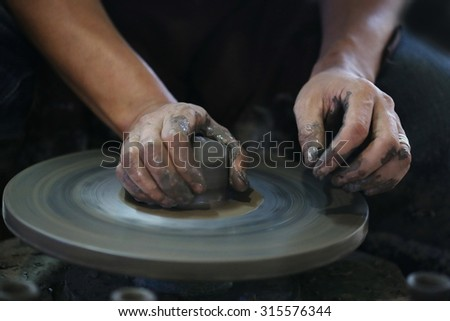 Hands working sculpture on pottery wheel ,Clay potter artwork on wheel, handmade and craft earthenware product factory ,making hands shaping a bowl pottery on the spinning,mold, Thailand