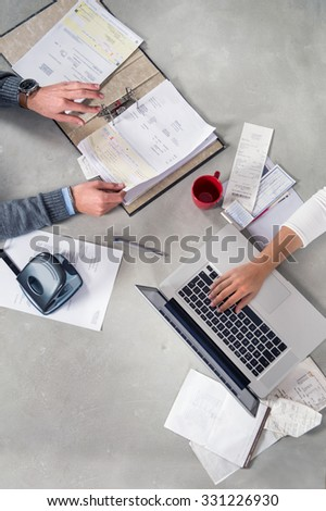 Hands, working with various kinds of paperwork, such as bills, receipts, invoices, doing accountancy with a laptop, seen from above on a concrete table surface - stock photo