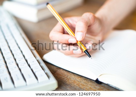 Hands writes a pen in a notebook (computer keyboard, a stack of books in background) - stock photo