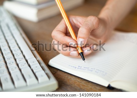 Hands writes a pen in a notebook, computer keyboard in background