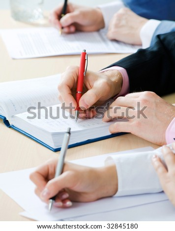 Hands writing notes