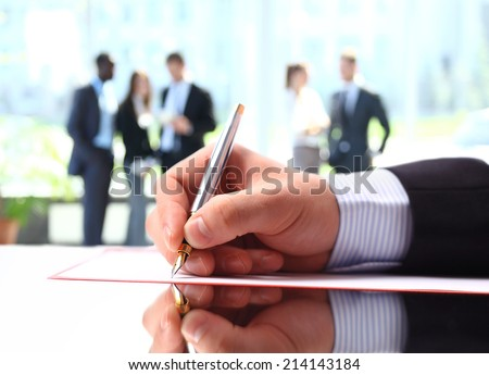 Hands writing on a paper while business people team work during conference  - stock photo
