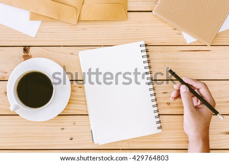 Hands writing on a wooden table with office supplies
