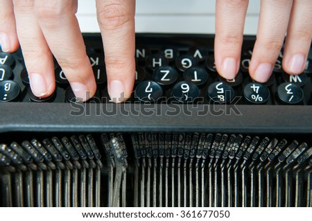 Hands writing on an old typewriter keyboard with focus on the metal letters - stock photo