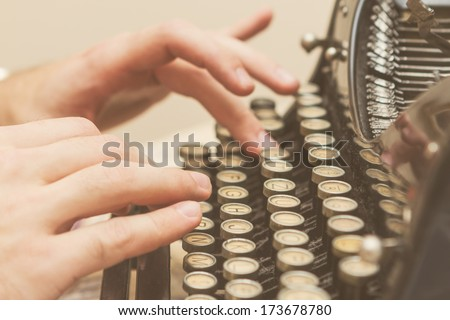 Hands writing on old typewriter - stock photo