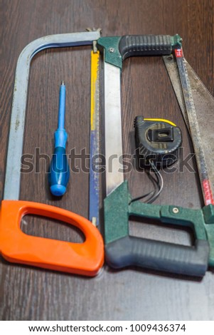 handsaws, screwdriver and measuring tape on wooden background