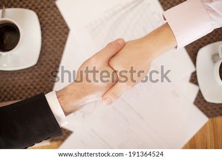 Handshake across the table. Meeting around a boardroom table. Two individuals shaking hands.  - stock photo