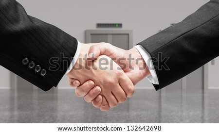 handshake and elevator on background - stock photo