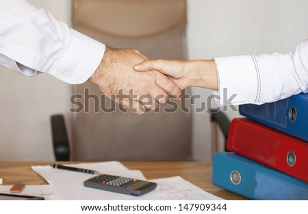 Handshake between a businessman and a business woman - stock photo