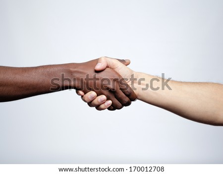 Handshake between african and a caucasian man over gray background - stock photo