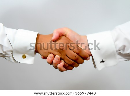 Handshake between black and white ethnic smartly dressed business men showing diversity and togetherness illustration like cartoon effect