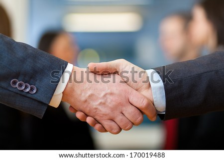 Handshake between businessman in a modern office - stock photo