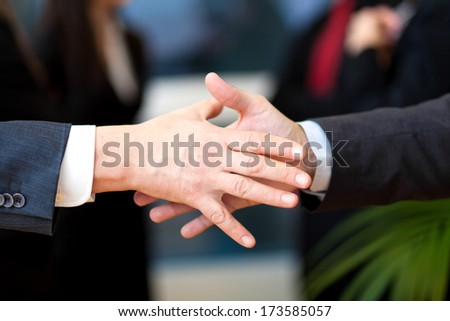 Handshake between businessman in a modern office