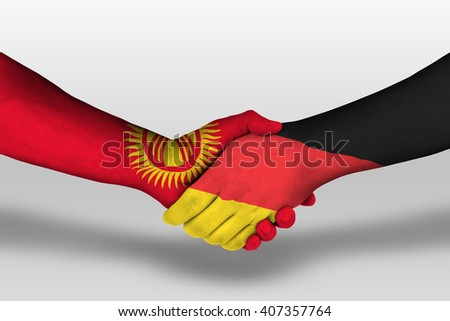 Handshake between germany and kyrgyzstan flags painted on hands, illustration with clipping path.