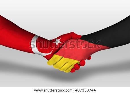 Handshake between germany and turkey flags painted on hands, illustration with clipping path.