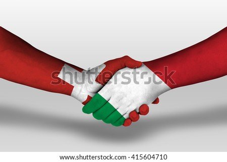 Handshake between italy and switzerland flags painted on hands, illustration with clipping path. - stock photo