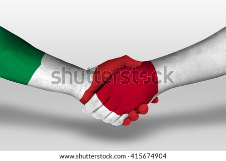 Handshake between japan and italy flags painted on hands, illustration with clipping path. - stock photo