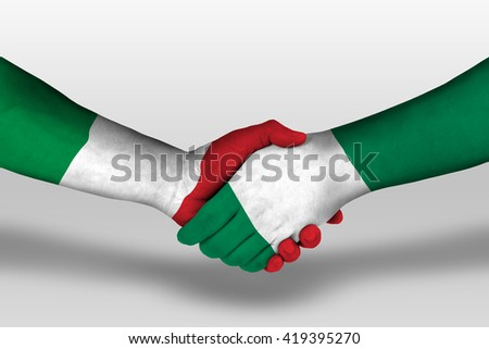 Handshake between nigeria and italy flags painted on hands, illustration with clipping path. - stock photo