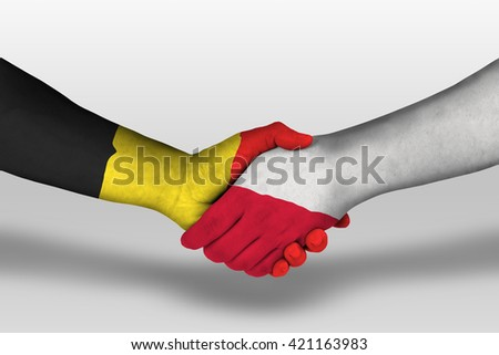 Handshake between poland and belgium flags painted on hands, illustration with clipping path.
