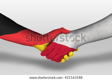 Handshake between poland and germany flags painted on hands, illustration with clipping path.