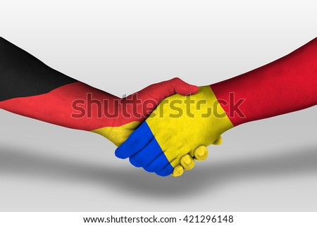 Handshake between romania and germany flags painted on hands, illustration with clipping path.