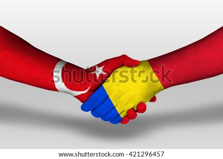Handshake between romania and turkey flags painted on hands, illustration with clipping path.