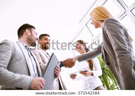 Handshake between two business executives.Image of four successful business partners working at meeting in office.They are working on a new project. - stock photo
