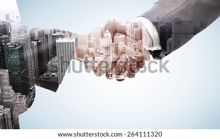 Handshake between two business people against high angle view of city - stock photo