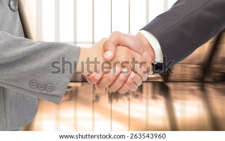 Handshake between two business people against room with large window looking on city - stock photo