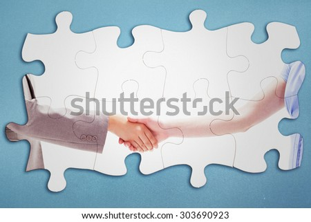 Handshake between two women against blue background