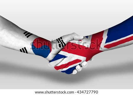 Handshake between united kingdom and south korea flags painted on hands, illustration with clipping path. - stock photo