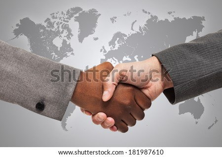 Handshake between white and black business people - stock photo