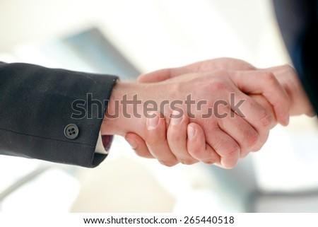 Handshake business partners. Two Confident businessman shake hands with each other in the business office view from below