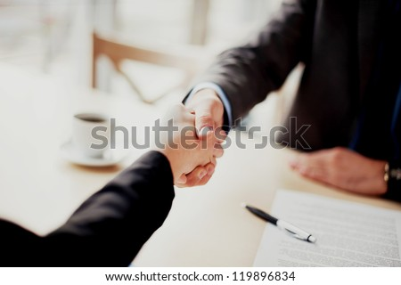 Handshake closeup of businesswoman and businessman. - stock photo